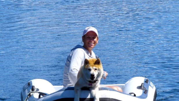 The author pilots her tender with Sally perched on the pontoons.