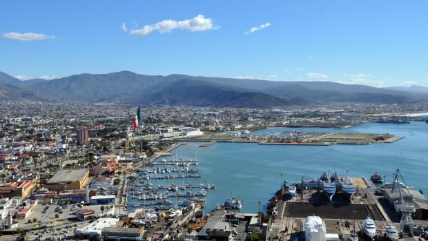 An enormous Mexican flag waves over the Ensenada waterfront. Today, there are no cruise ships calling, so from out to sea, the flag and pinkish hotel nearby serve as beacons for the harbor.