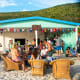 The party starts early, around noon, as visitors order drinks, swim, and relax at the tables outside The Soggy Dollar beach bar.