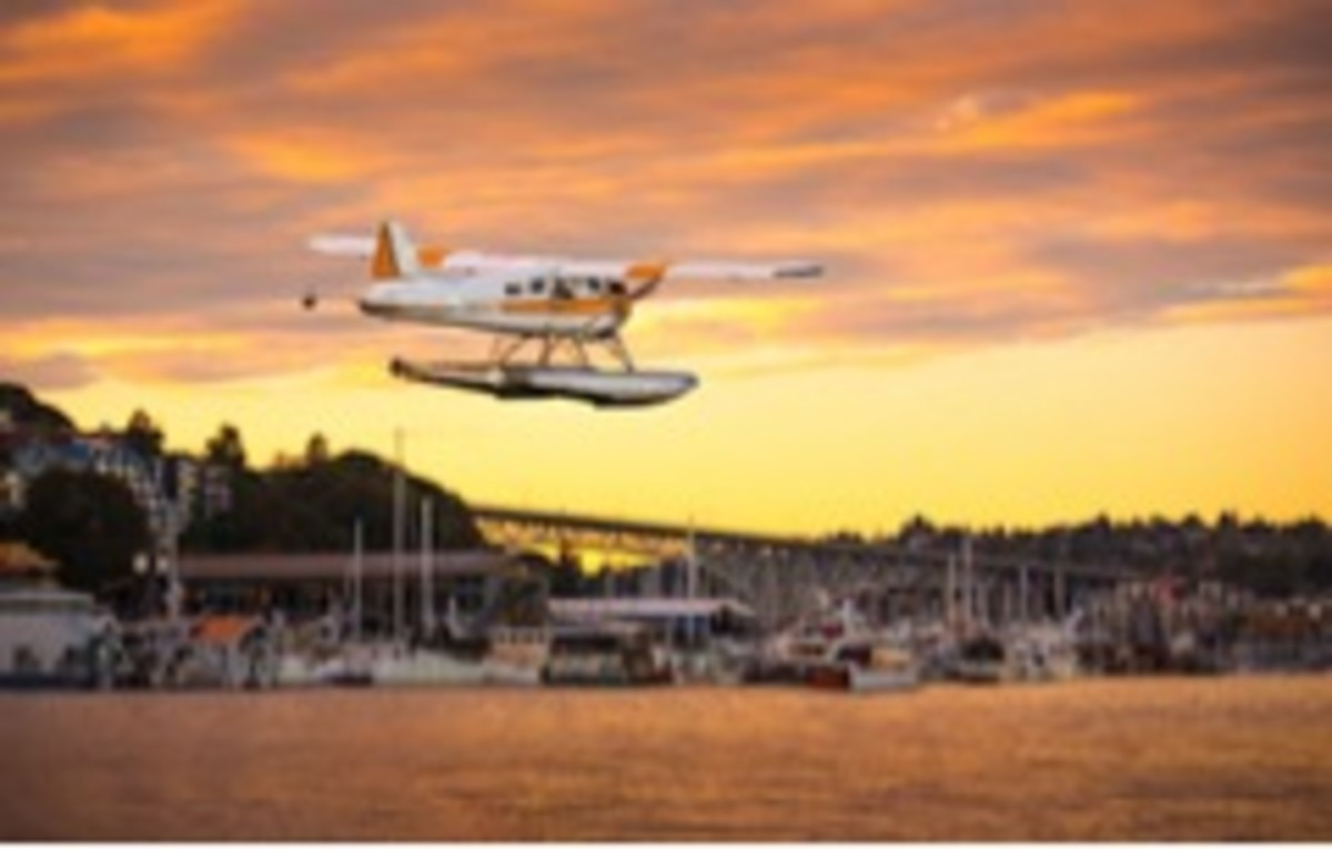 A seaplane lands at Lake Union as sun sets.