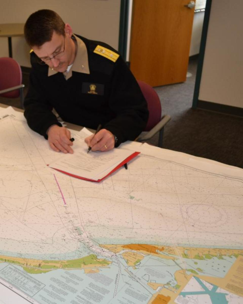 Rear Adm. Gerd Glang certifies a new print-on-demand chart agent after inspecting the company's sample chart.