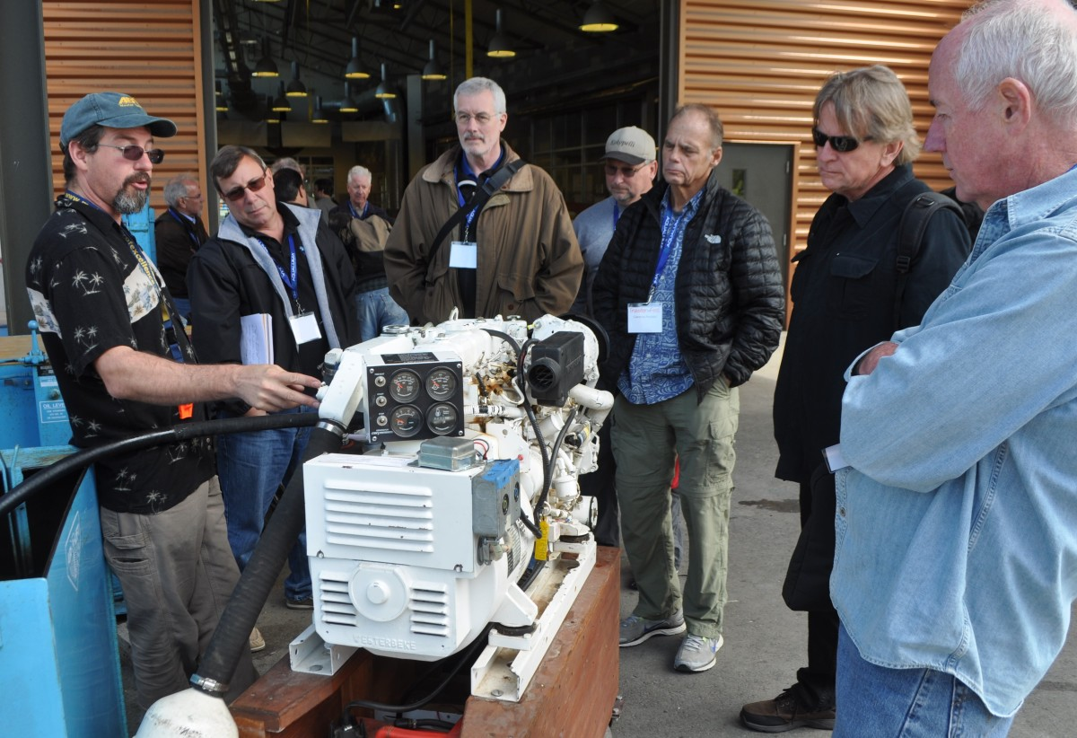 "Mike Beemer of Northwest Center for Excellence for Marine Manufacturing & Technology of Anacortes, a TrawlerFest partner, gives ""Diesel Engines"" attendees some hands-on training at the 2015 event."