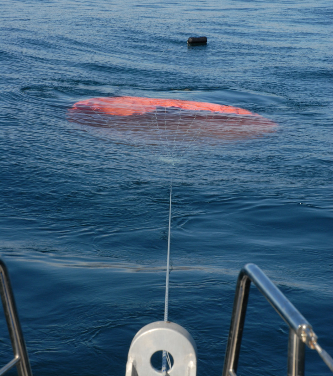 A parachute Sea Anchor deployed from the bow pulpit of a trawler.