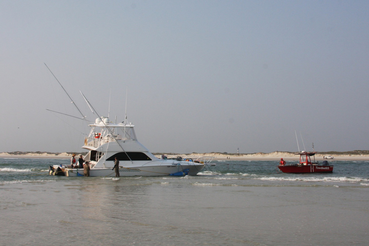 Salvors walk in barely knee-deep water around a beached Hatteras. The vessel would eventually be rescued from peril.
