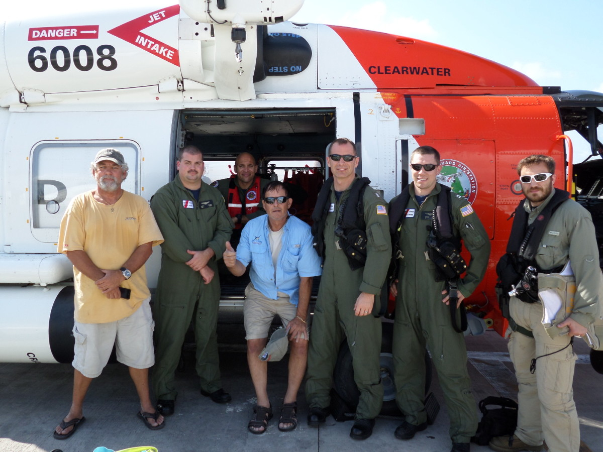 The two rescued boaters in plain clothes pictured with the Jayhawk rescue crew.