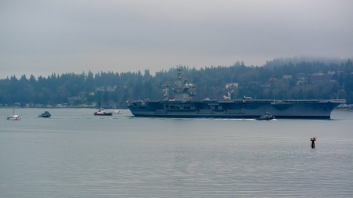 The crews of the 87-foot Coast Guard Cutters Osprey and Swordfish escort the Navy supercarrier USS Nimitz into their new homeport of Bremerton, Wash., Jan. 13, 2015. The Coast Guard provides for the security of Naval vessels through escorts and enforcement of security zones nationwide. (Photo courtesy Clint Mooers)