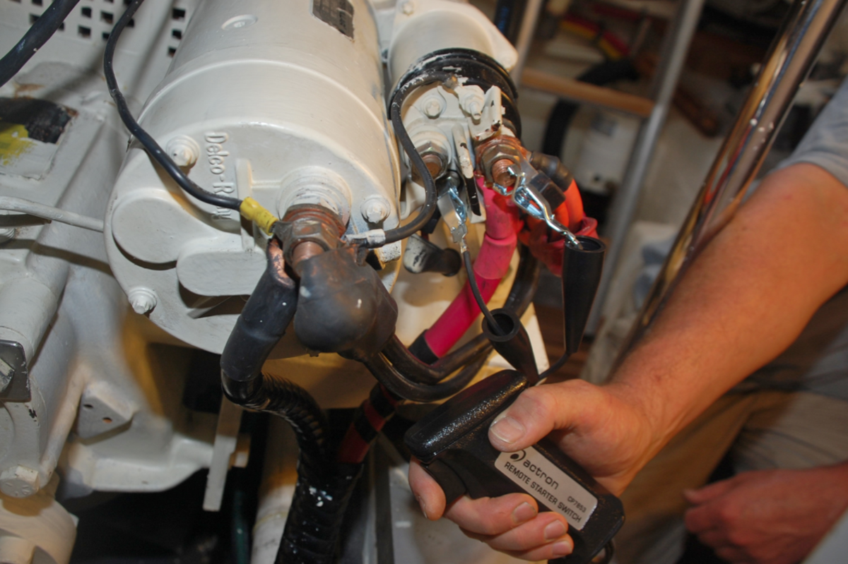 A mechanic is using a remote starter switch to bypass the failed control circuit.
