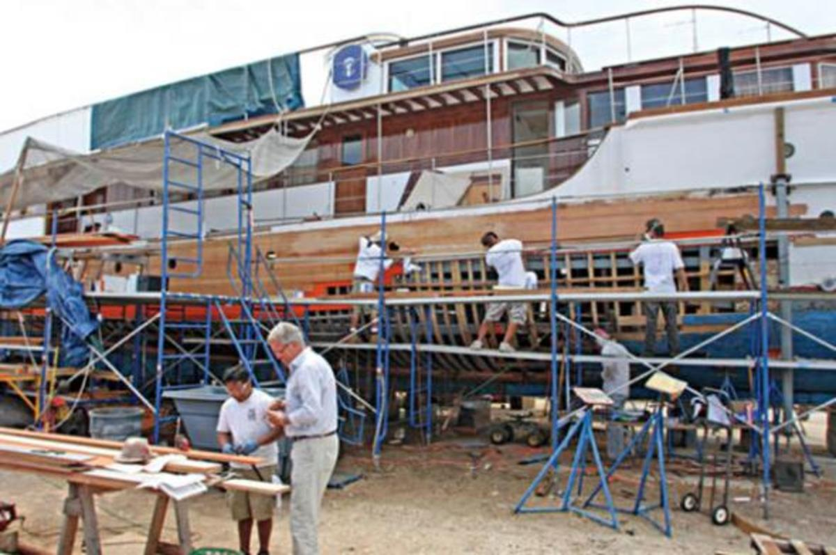 "Jim Moores, foreground, second from left, and his team engage in some ""backwards boatbuilding"" on Honey Fitz 's starboard hullside. (Moores Marine)"