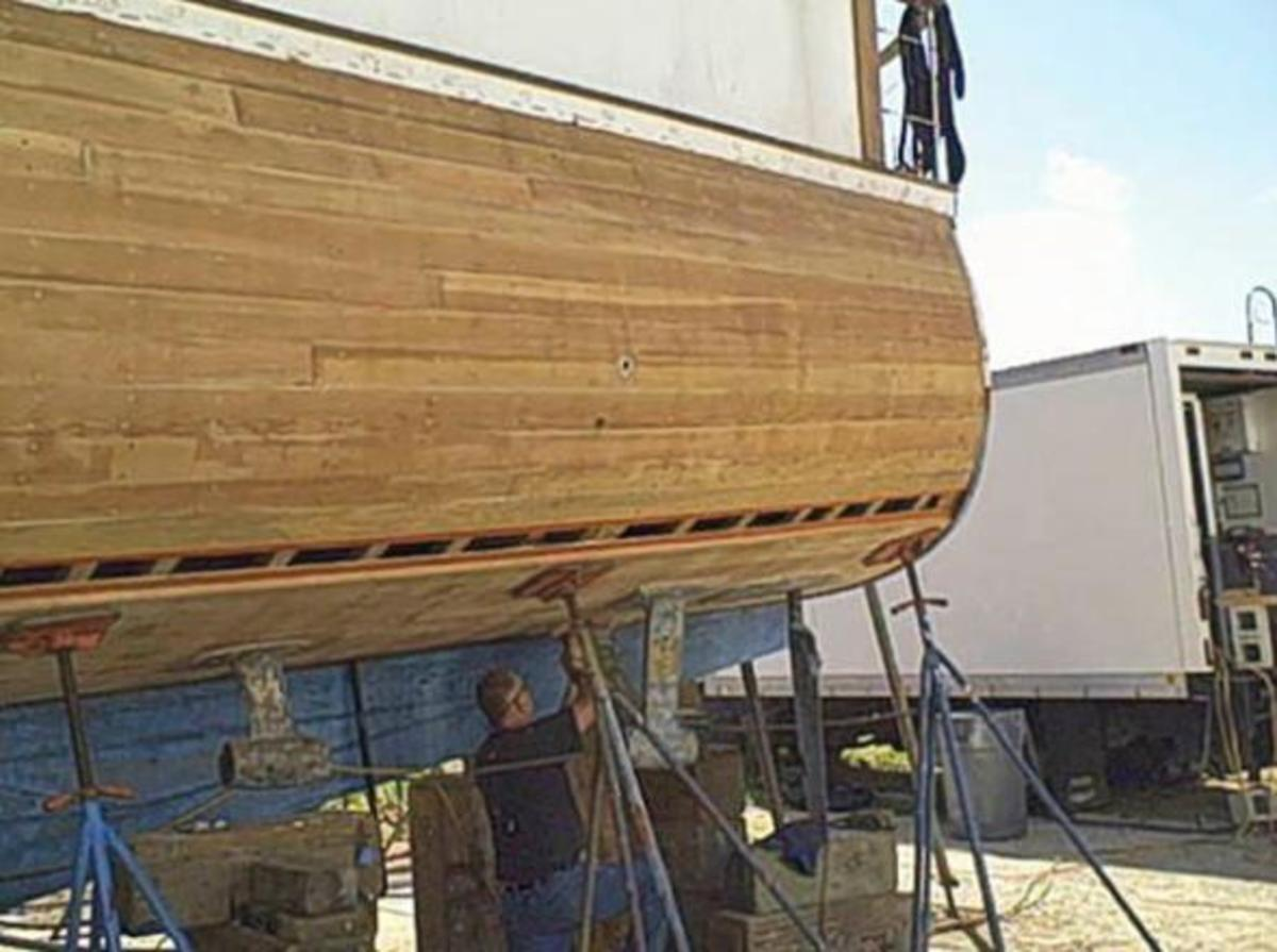 Workers repanel the yachts wooden hull. (Moores Marine)