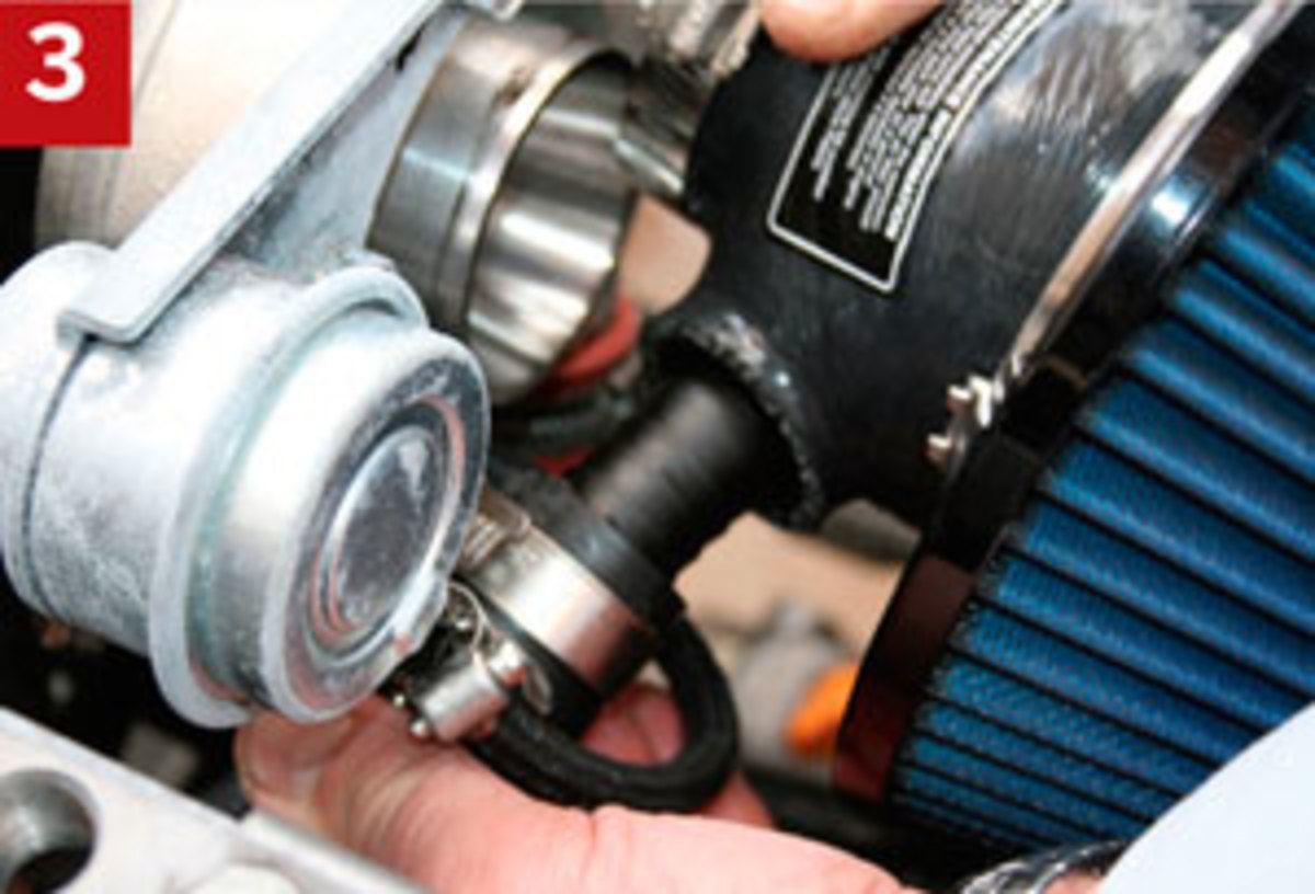 We attach the breather hose then tighten its clamp.