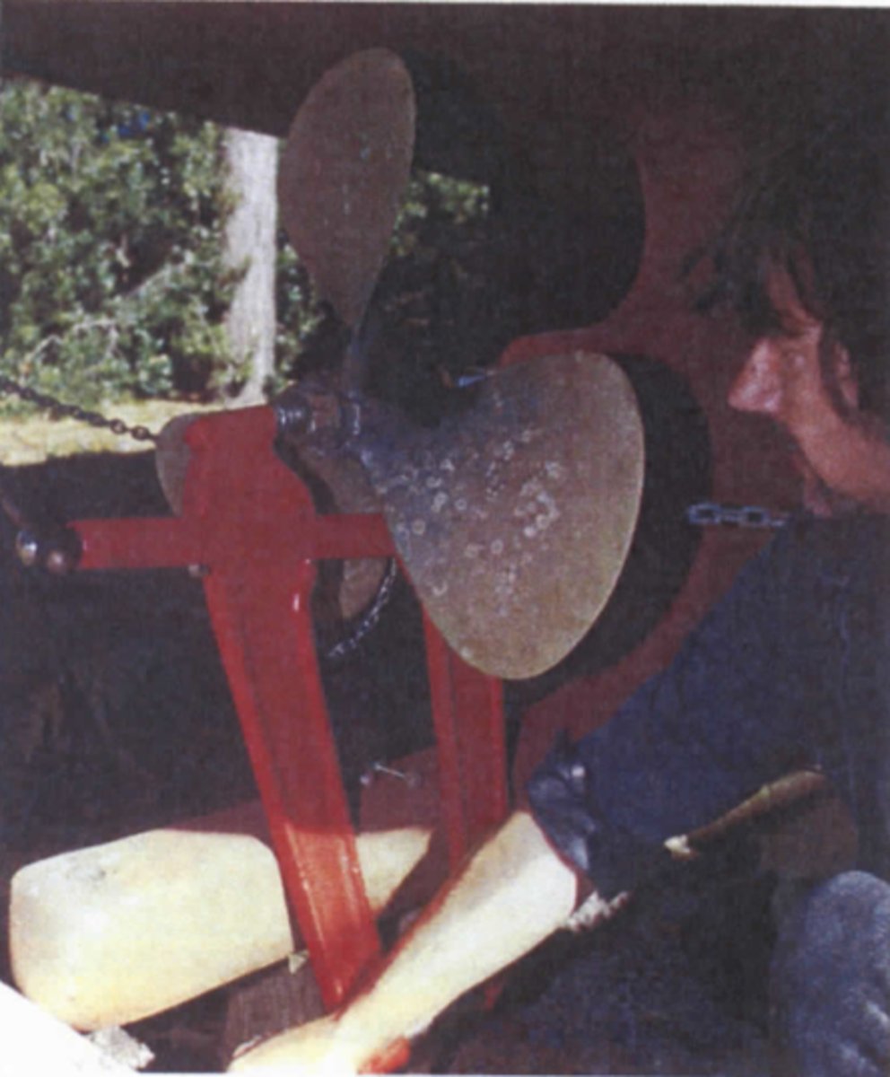 Propeller removal using a tool designed specifically for prop removal. Notice that the nut is loosely screwed onto the shaft, to prevent the propeller from falling once it releases its grip on the shaft.