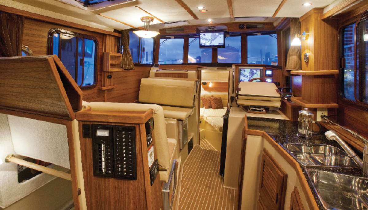 The Ranger Tugs 31 maximizes saloon and helm space with a number of tricks, including a dinette seat that reverses into a forward-facing companion seat, a compact second stateroom beneath the dinette and a helm chair (atop the fridge cabinet) that folds away when not in use or rotates for socializing with guests.
