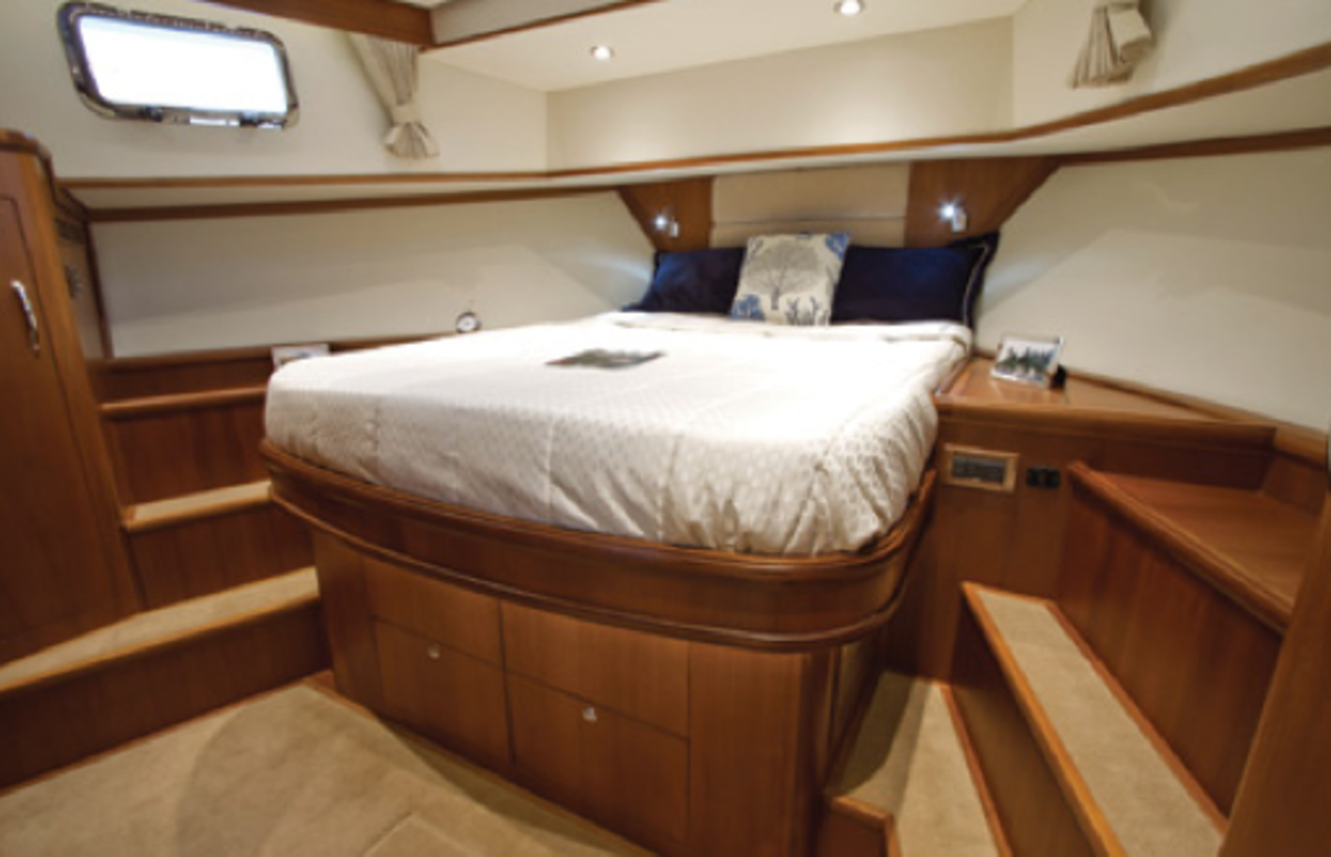 Queen berths forward tend to be high. Grand Banks has addressed this with port and starboard step-ups. Fabric and headliner help create a light and airy atmosphere, which plays against the hardwood panels and furniture.