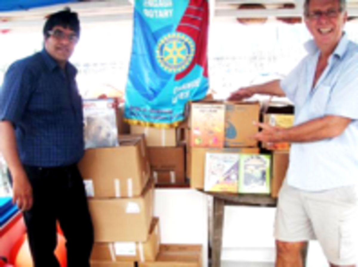 The President of the Rotary Club of San Fernando, Kurt Traboulay handing over the books.