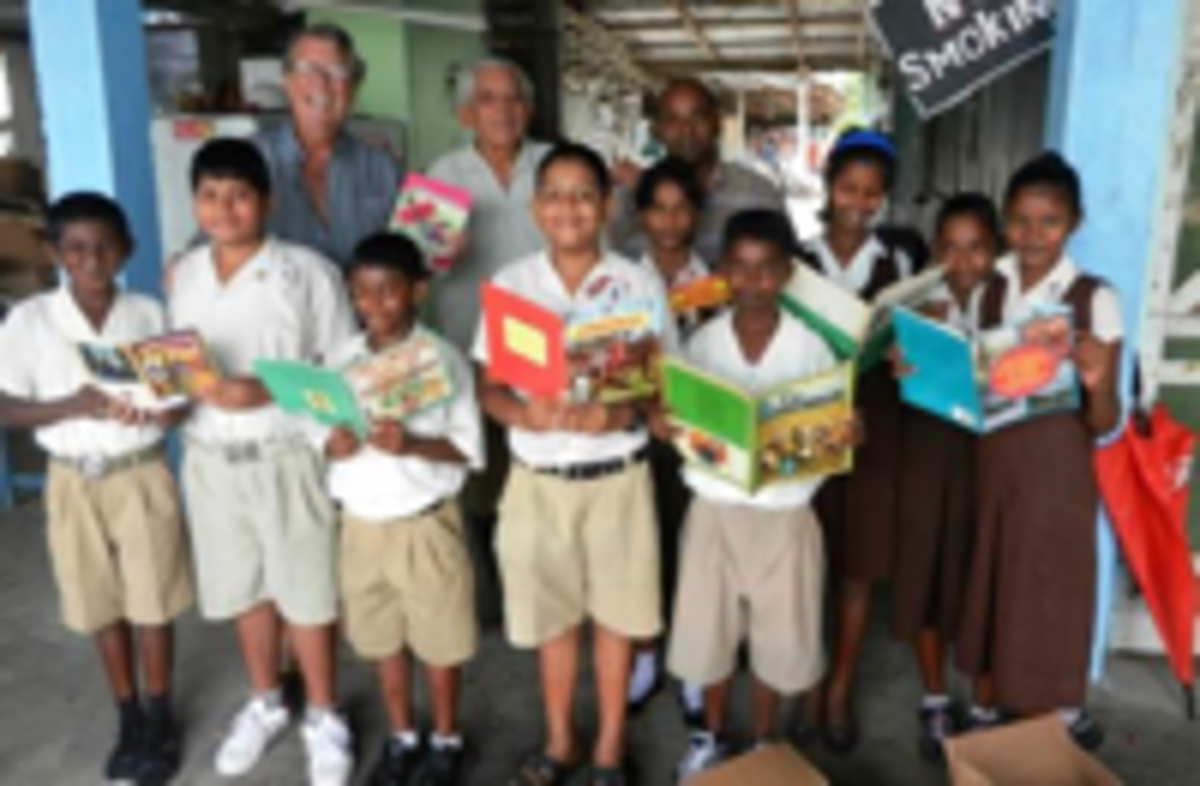 Above and Below: Quentrall-Thomas is pictured with Guyana's shcool kids and their new textbooks.