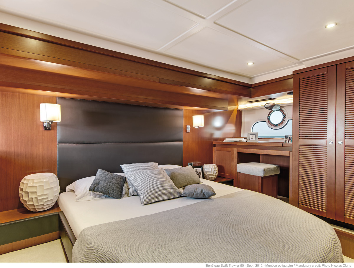 The full-beam master stateroom features warm mahogany paneling, a spacious double island berth and two large portlights fitted with opening ports.