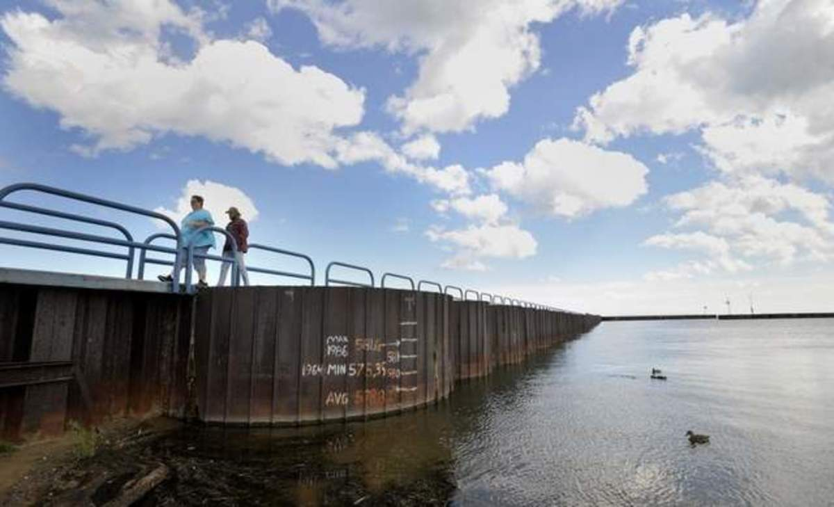 Graffiti on a submerged wall illustrates the change in lake water levels. (Photo by Todd McInturf / Detroit News)