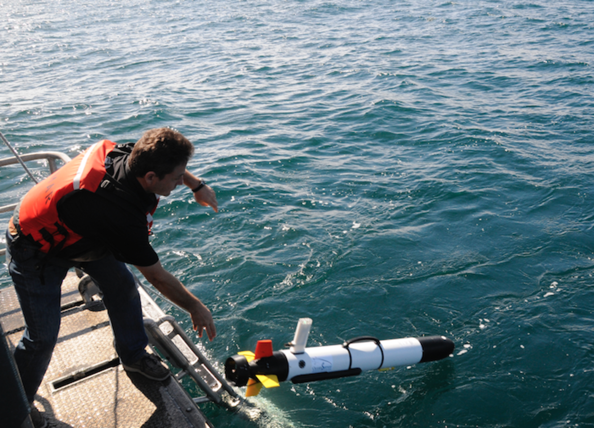 Teledyne SeaBotix's operator Cyril Poissonnet launches an autonomous underwater vehicle (AUV) off the stern of the research vessel Fulmar during the October 2015 expedition to the USS Conestoga shipwreck. (Robert V. Schwemmer, NOAA ONMS)