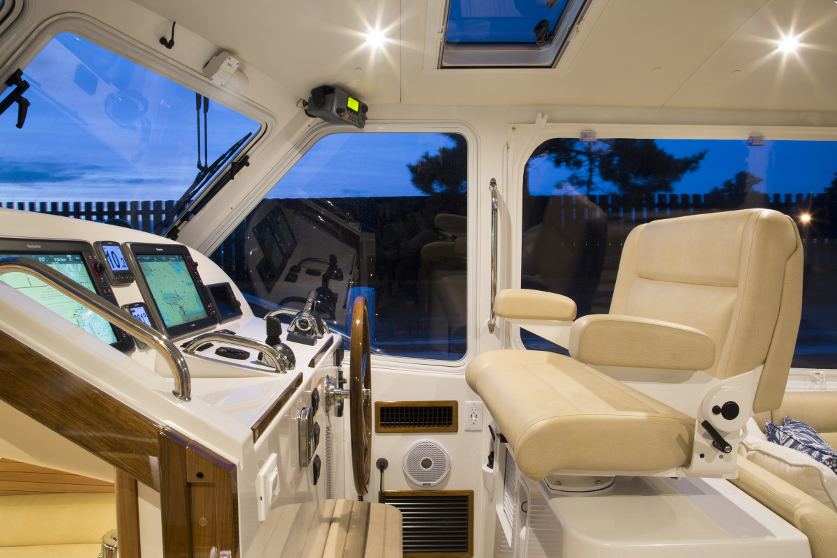 A shippy wheel, Volvo Penta IPS joystick, a pair of Raymarine screens, and a Stidd helm bench seat mean you won't be wanting for anything.