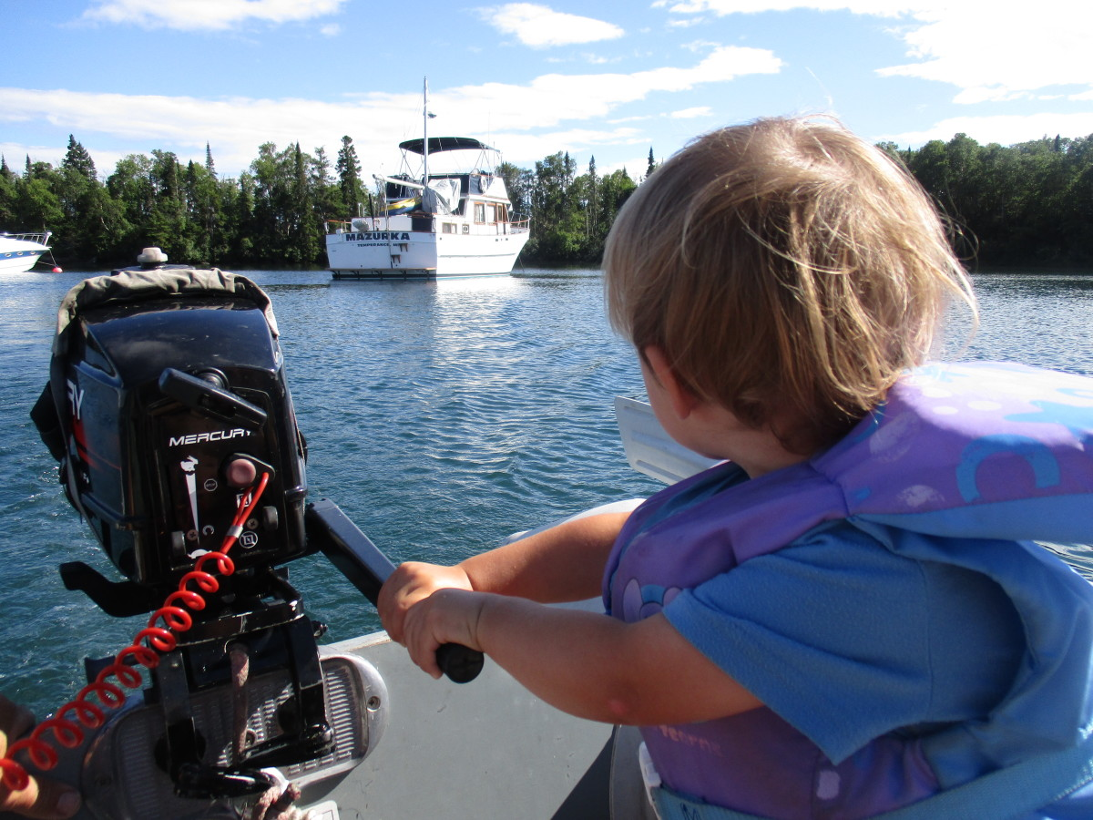 Two-year-old Anton learns to steer the Zodiac at Isle Royale.