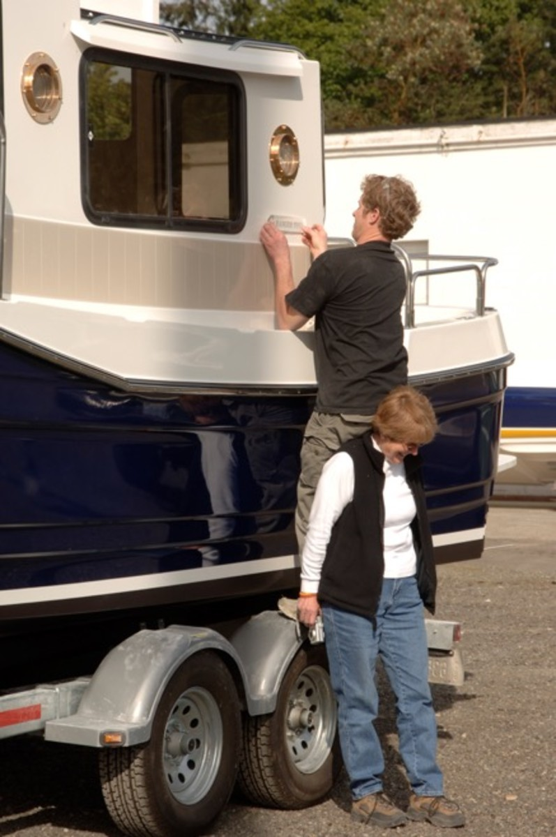 David Livingston Jr (Dave Sr's son) leaning on his Aunt Lin's (Dave Sr's sister) back to apply a decal on the new tug.