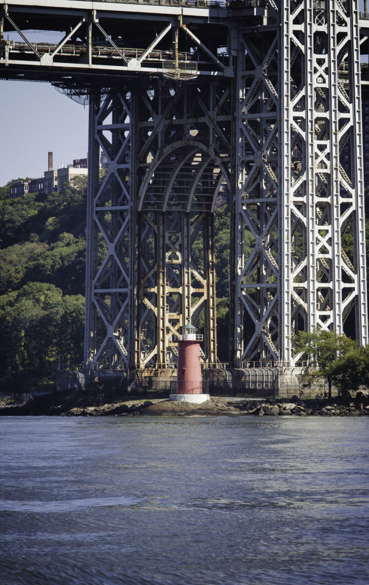 The famous Jeffrey's Hook Light (aka, The Little Red Lighthouse) dwarfed by the George Washington Bridge on the Hudson River.