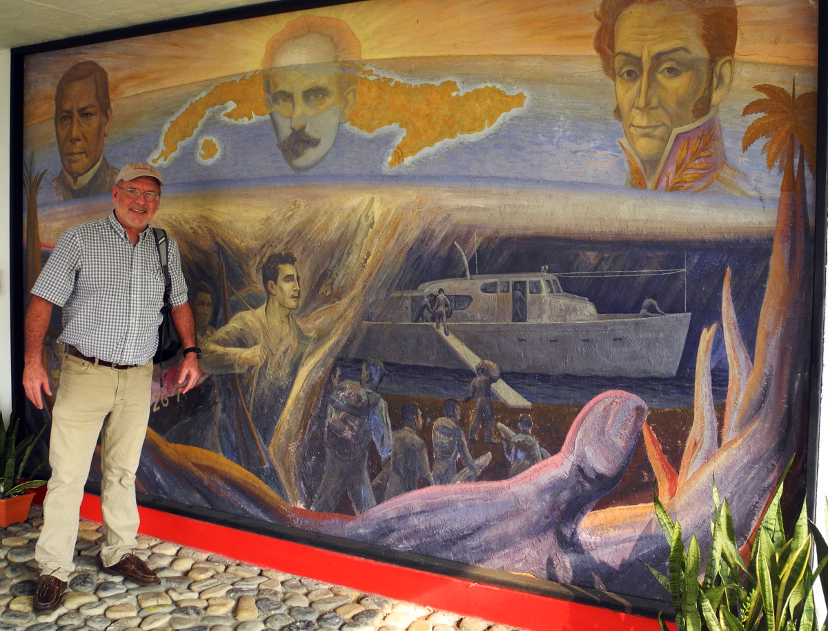The author poses with a mural in Tuxpan, Mexico, depicting Granma's provisioning prior to the 1956 expedition.