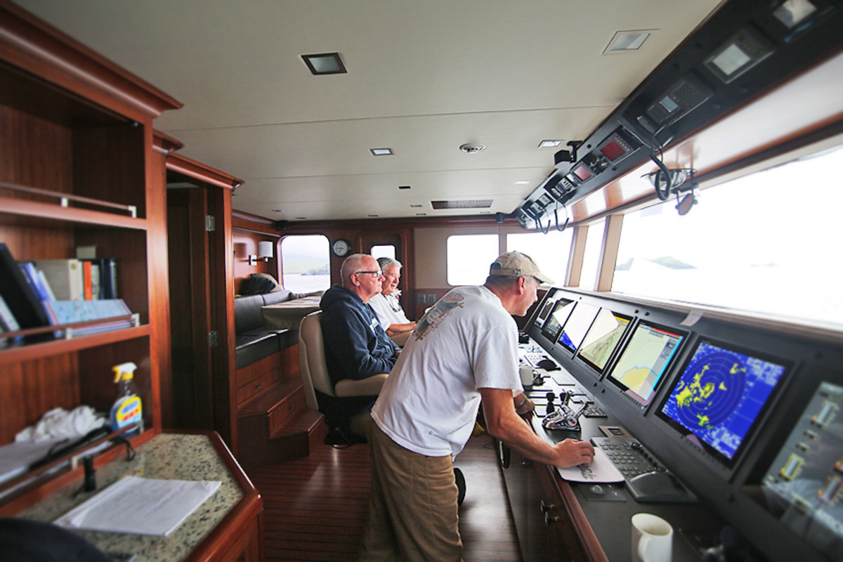 Jim Leishman, seated at center, at the helm of the Nordhavn 120 during delivery.