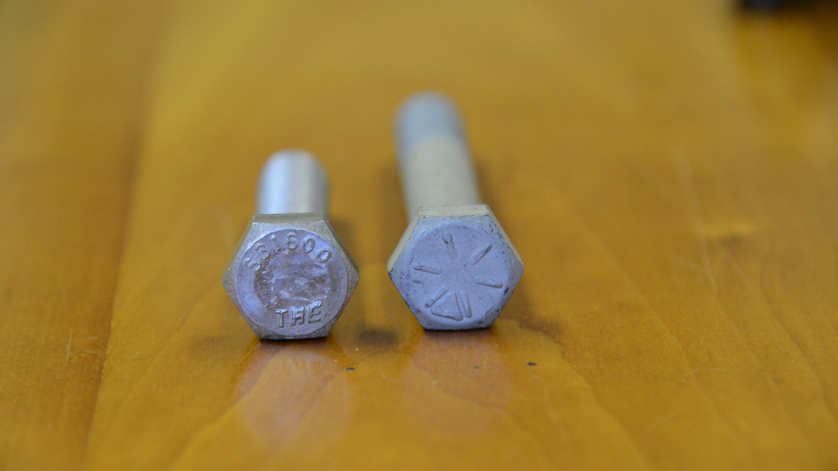 The bolt on the left has its grade—316—stamped on the head . The six radial lines on the bolt to the right indicate Grade 8.