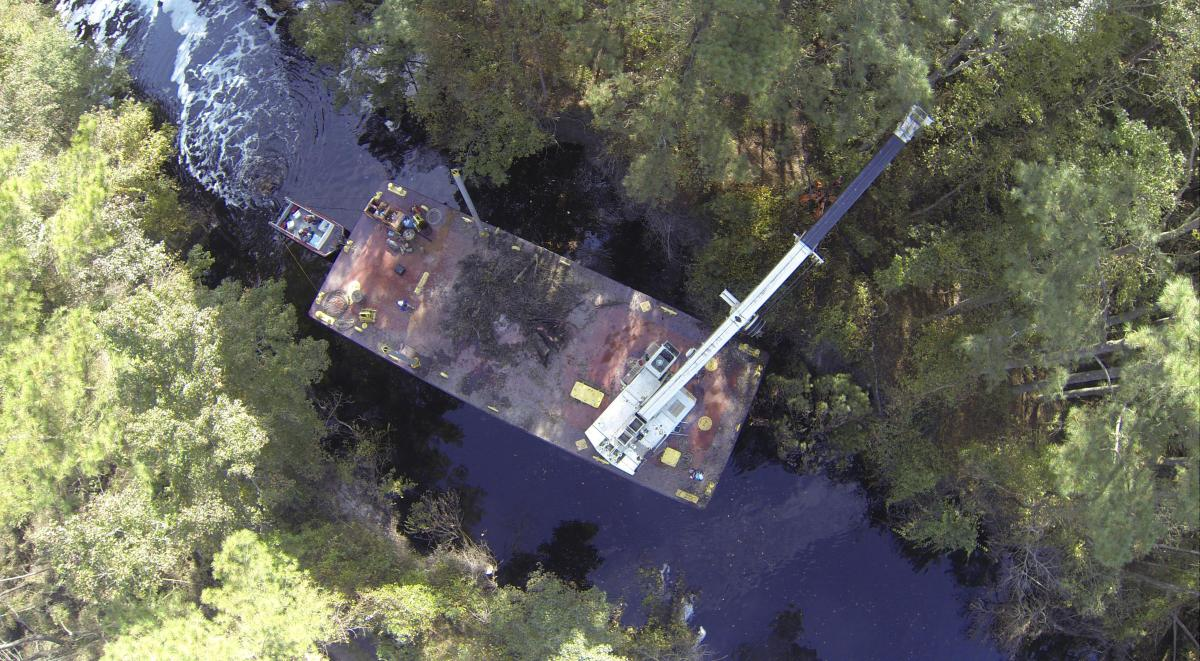 Norfolk District Operations Branch personnel use a crane barge to remove downed trees along the Dismal Swamp Canal's Lake Drummond feeder ditch here October 27,2016. The trees came down during Hurricane Matthew, which inundated the area with water causing flooding, power outages and downed trees. (U.S. Army photo/Patrick Bloodgood)