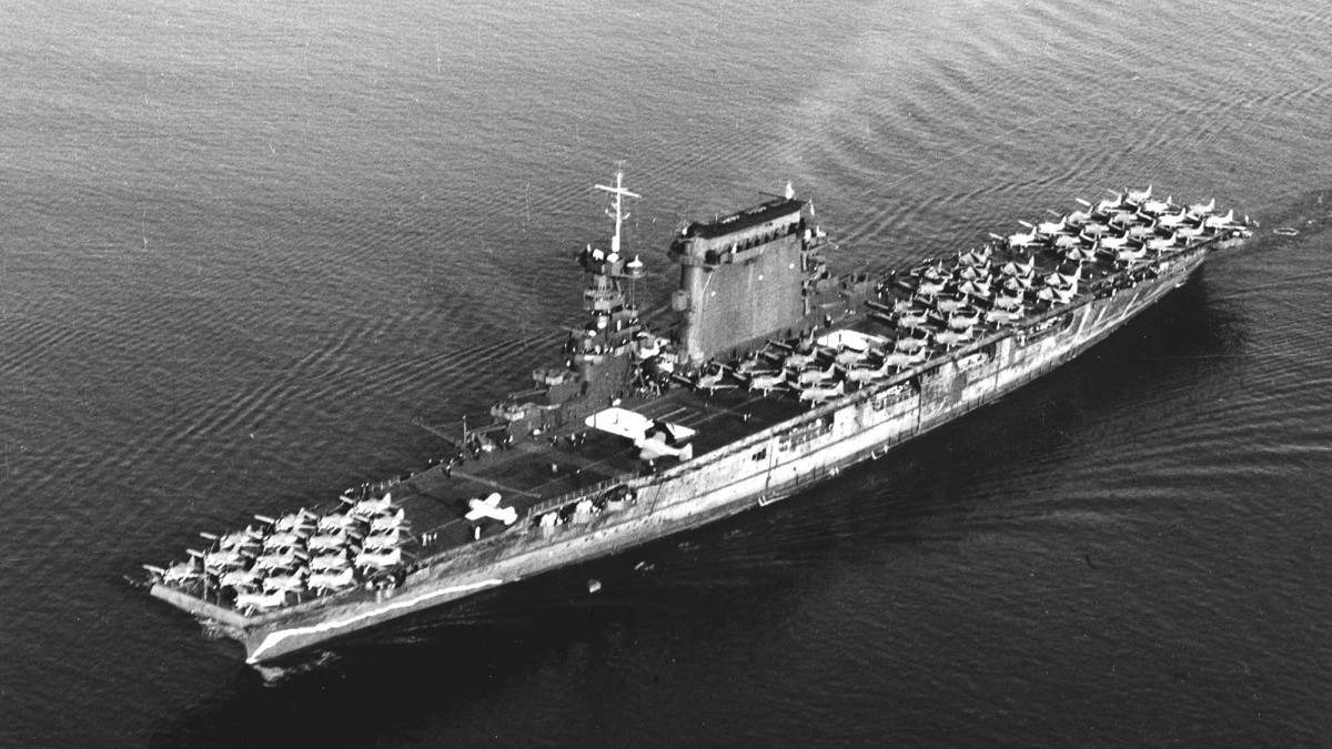 The U.S. Navy aircraft carrier USS Lexington (CV-2) leaving San Diego, California (USA), on 14 October 1941. Planes parked on her flight deck include Brewster F2A-1 fighters (parked forward), Douglas SBD scout-bombers (amidships) and Douglas TBD-1 torpedo planes (aft). Note the false bow wave painted on her hull, forward, and badly chalked condition of the hull's camouflage paint.