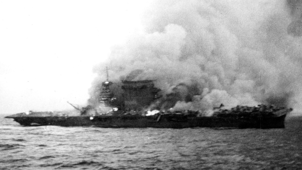 The U.S. Navy aircraft carrier USS Lexington (CV-2), burning and sinking after her crew abandoned ship during the Battle of Coral Sea, 8 May 1942. Note planes parked aft, where fires have not yet reached.