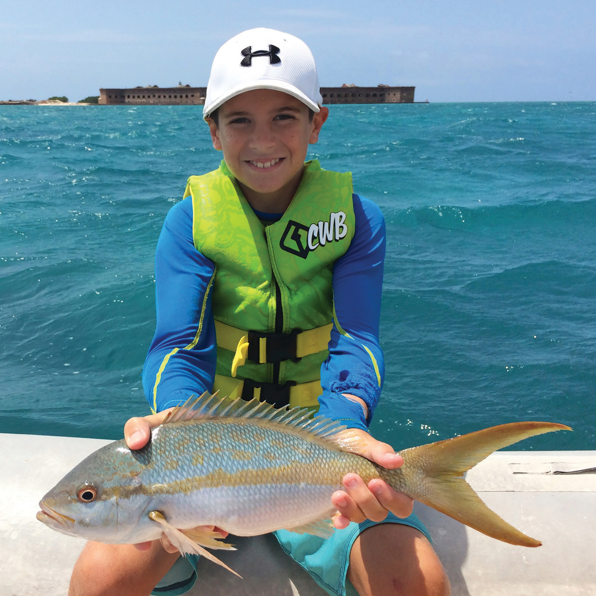 Corey catches a keeper yellowtail snapper with Fort Jefferson in the background.