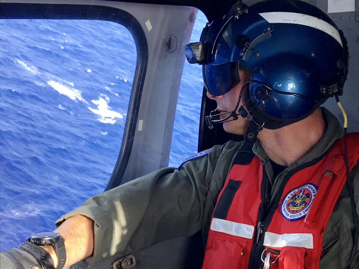 An aircrewman aboard a Coast Guard MH-65 Dolphin helicopter from Air Station Barbers Point scans the waters off Oahu Aug. 18, 2017, for any sign of five missing aviators from an Army UH-60 Black Hawk helicopter. The aviators went missing the night of Aug. 15 during a training evolution.