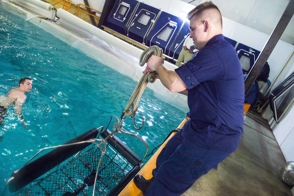 First Class Cadet Christian Breviario pulls the rescue basket from the water after he and his team tested their design at a simulation facility.