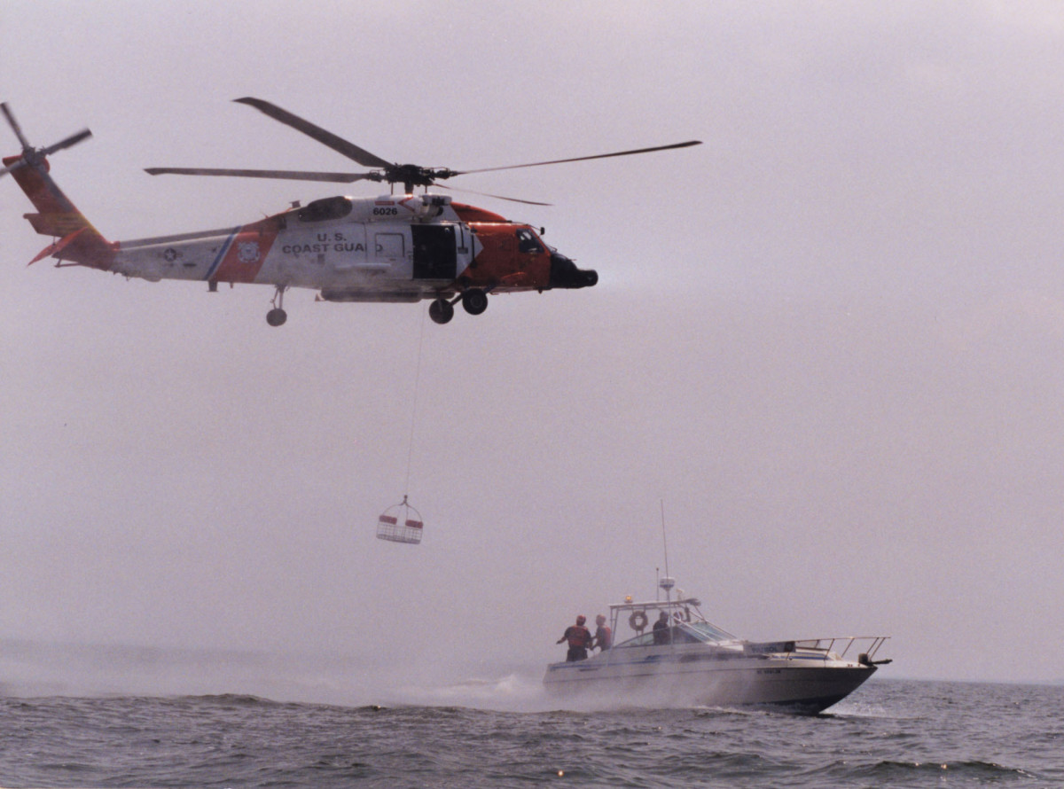 A Coast Guard HH-60J helicopter practices basket hoists with a Coast Guard Auxiliary boat.
