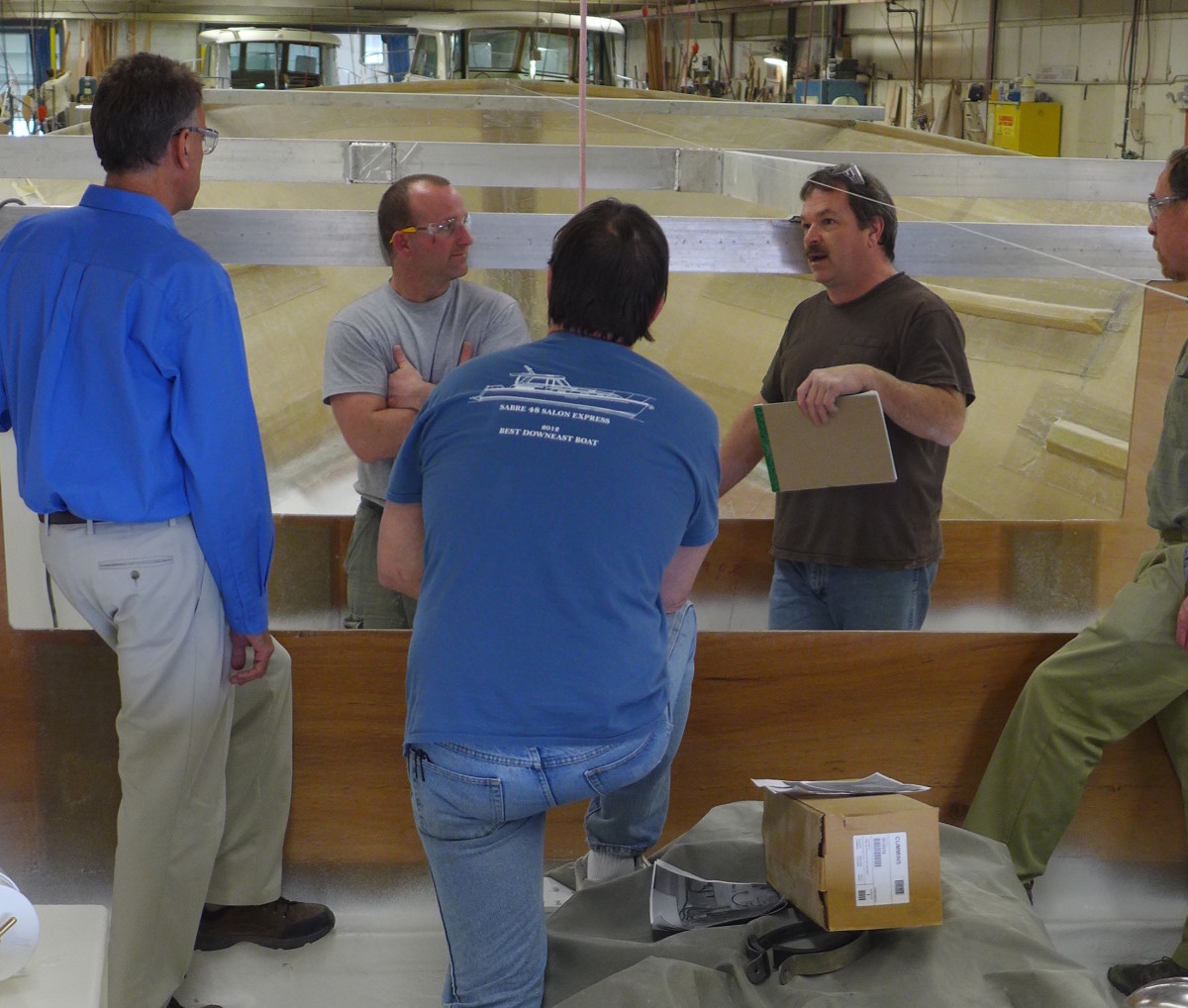 Employees discussing the construction of the Back Cove Downeast 37.