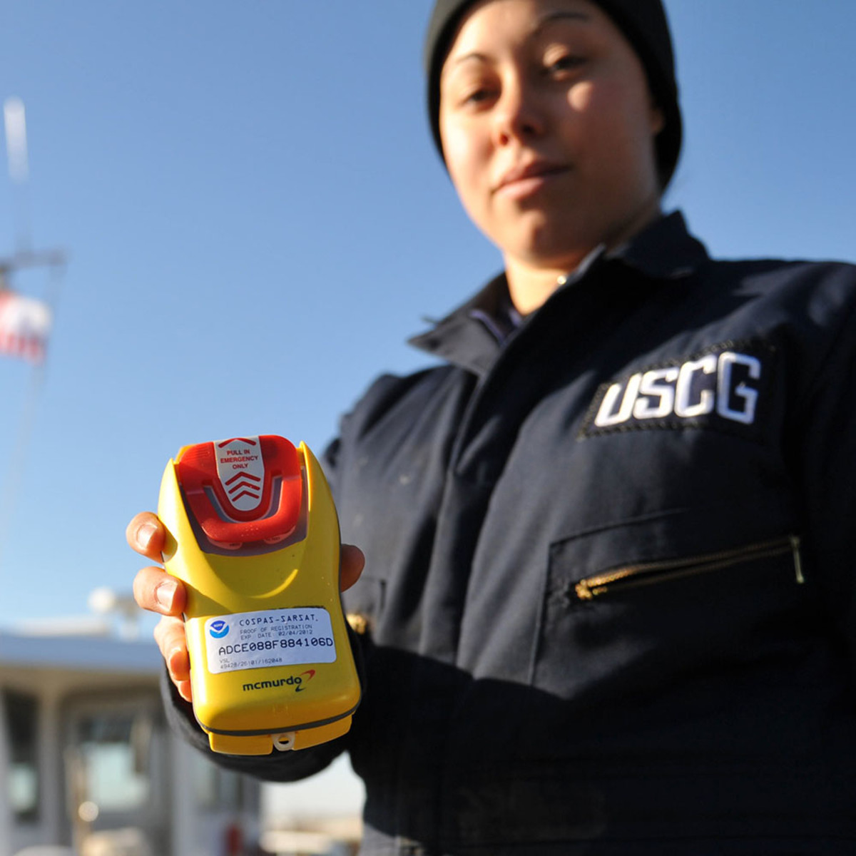 Seaman Ashleigh Wilson, a boatcrew member at Aids to Navigation Team Baltimore, holds a personal emergency position indicating radio beacon on a pier located in Curtis Bay, Md., Dec. 9, 2010. Crewmembers at ANT Baltimore carry PEPIRBs while servicing aids throughout the upper Chesapeake Bay.