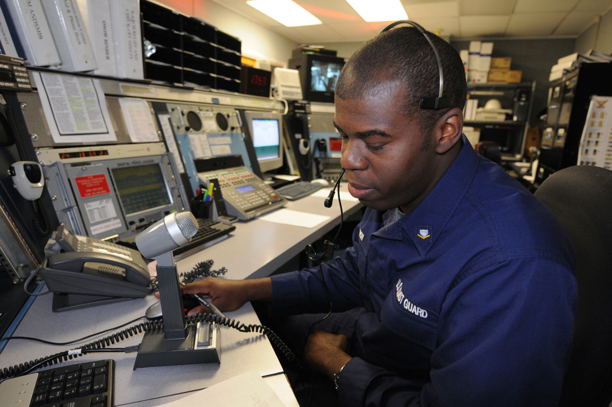 Petty Officer 3rd Class Robert Finch, an operational specialist at Coast Guard Sector Baltimore, Md., responds to a radio call while standing watch.