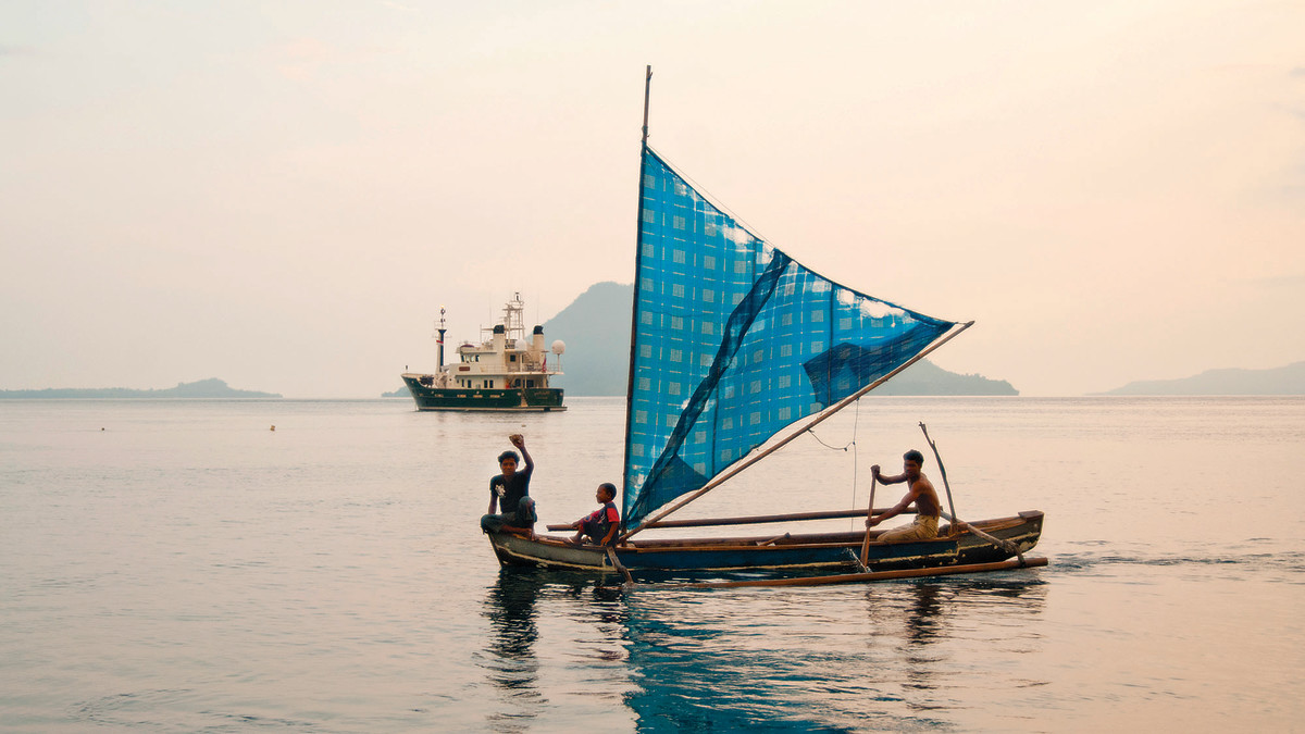 Sailing outriggers are still the best way to keep in touch among the thousands of Indonesian islands. Whale Song is anchored in the background.