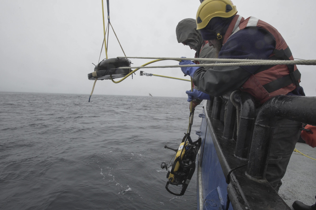 Team member Matt Breece lowers the project ROV over the side of Research Vessel Norseman II.