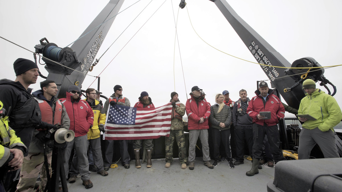 The project team and members of the crew of the R/V Norseman II conduct a wreath ceremony to honor the final resting place of the 71 Sailors lost on the USS Abner Read.