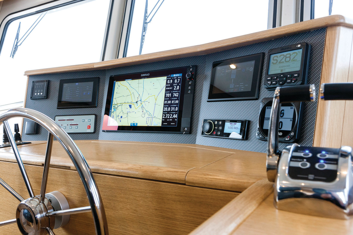 A Simrad display is flanked by small controls.