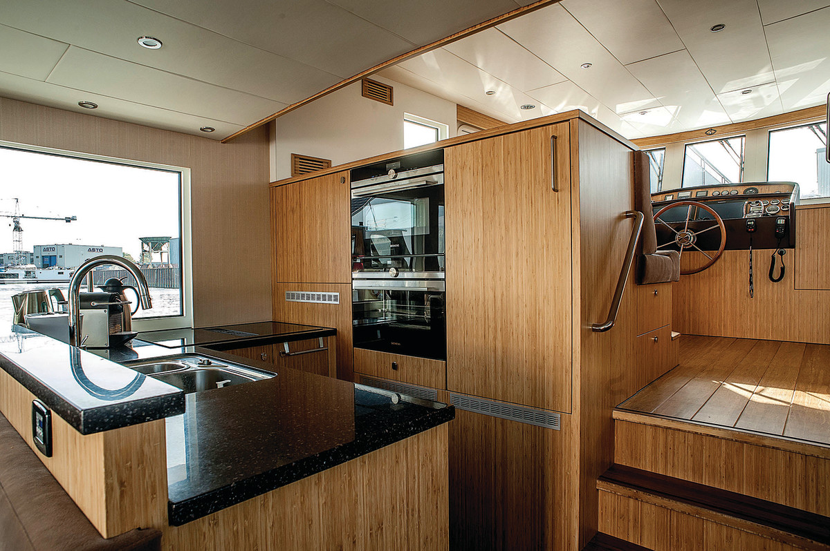 Sizeable L-shape galley and stowage options before the raised pilothouse.