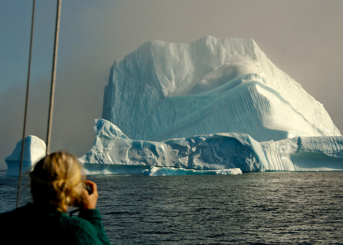 A giant iceberg emerges from hazy fog in Disko Bay. Below Left: Shore visits in Greenland are rarely lacking fascinations.