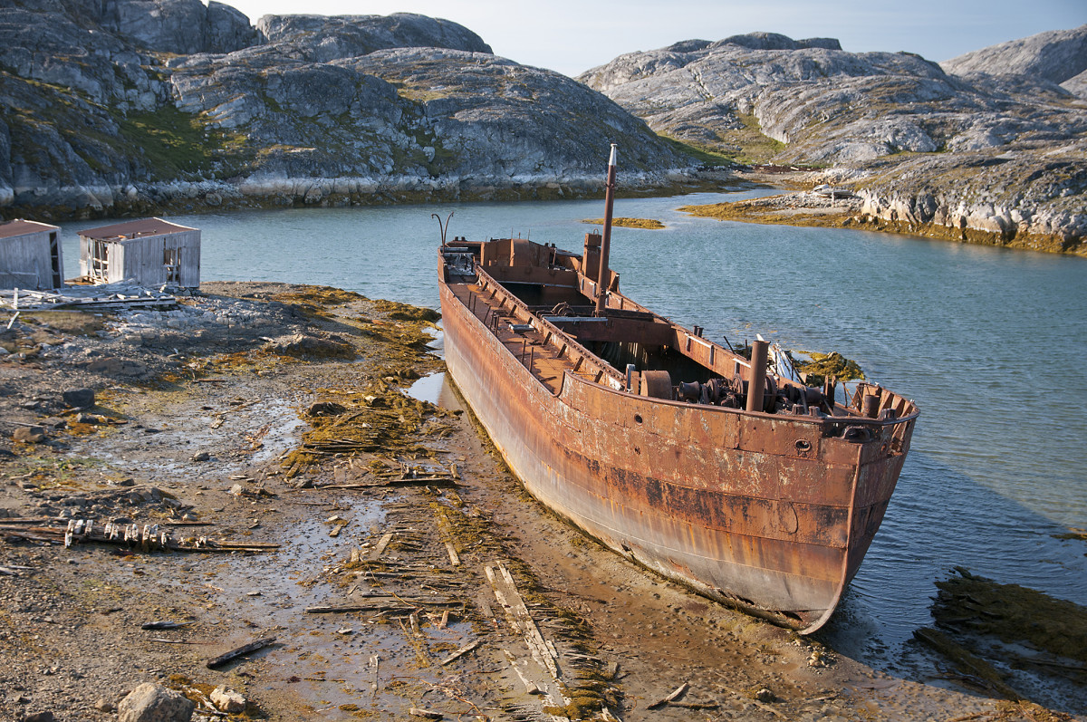 At the head of the bay, a derelict steel sailing ship rusts into oblivion.