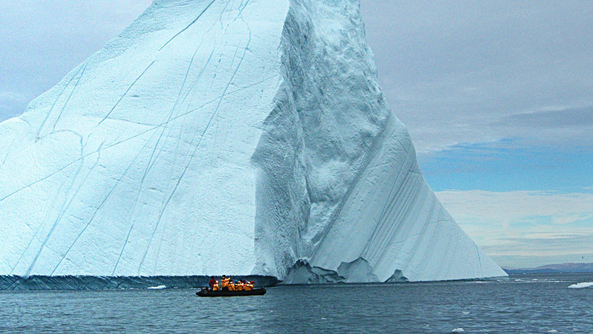 Our Zodiac is dwarfed by a towering iceberg—7/8ths of which is hidden beneath the water.