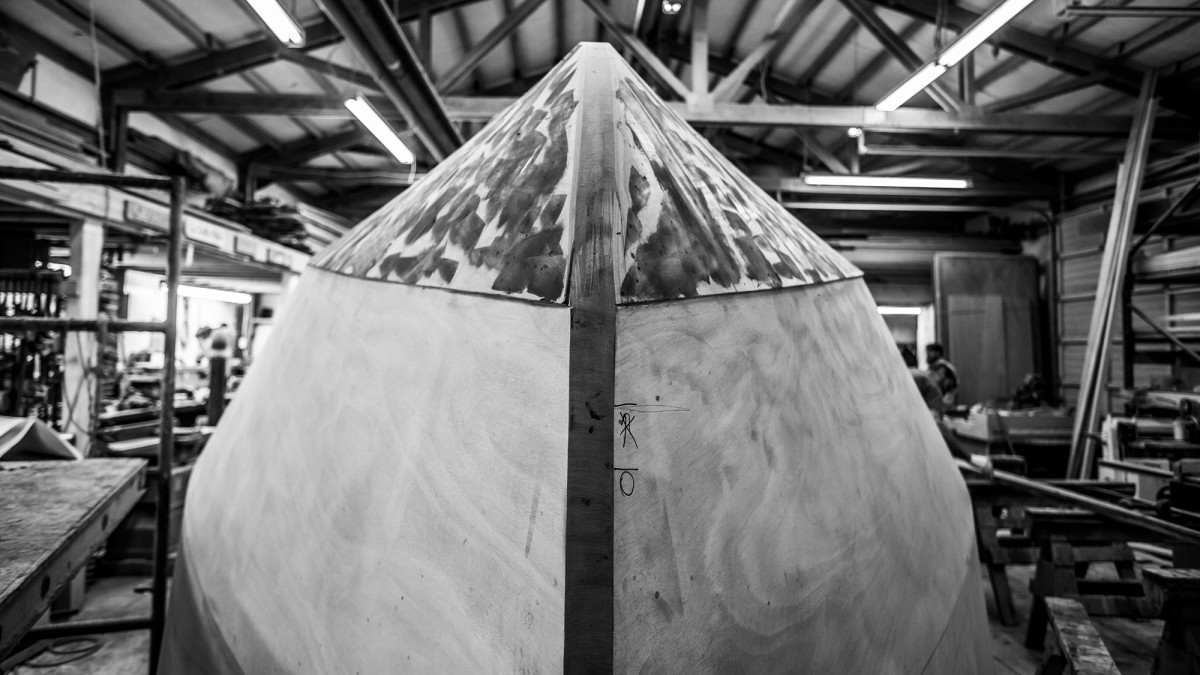 Kingfisher, in process, is still upside down as the hull bottom is sheathed to an extra thickness compared to the rest of the hull. After building up to the correct thickness, the boat will be primed before she is flipped right side-up for finishing.