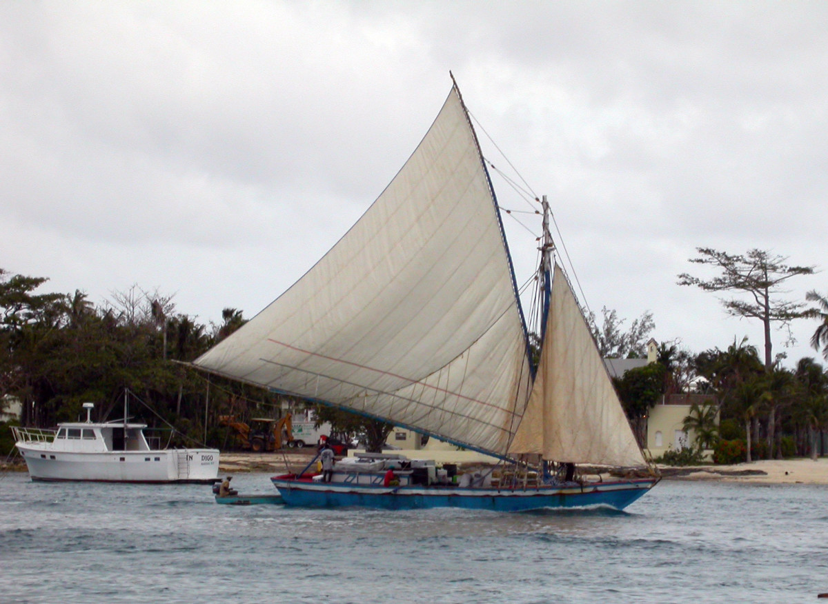 A Haitian sloop transits Nassau Harbour before the crackdown on illegal immigration. The push boat is a concession to Bahamian authorities. Most sloops are engineless.