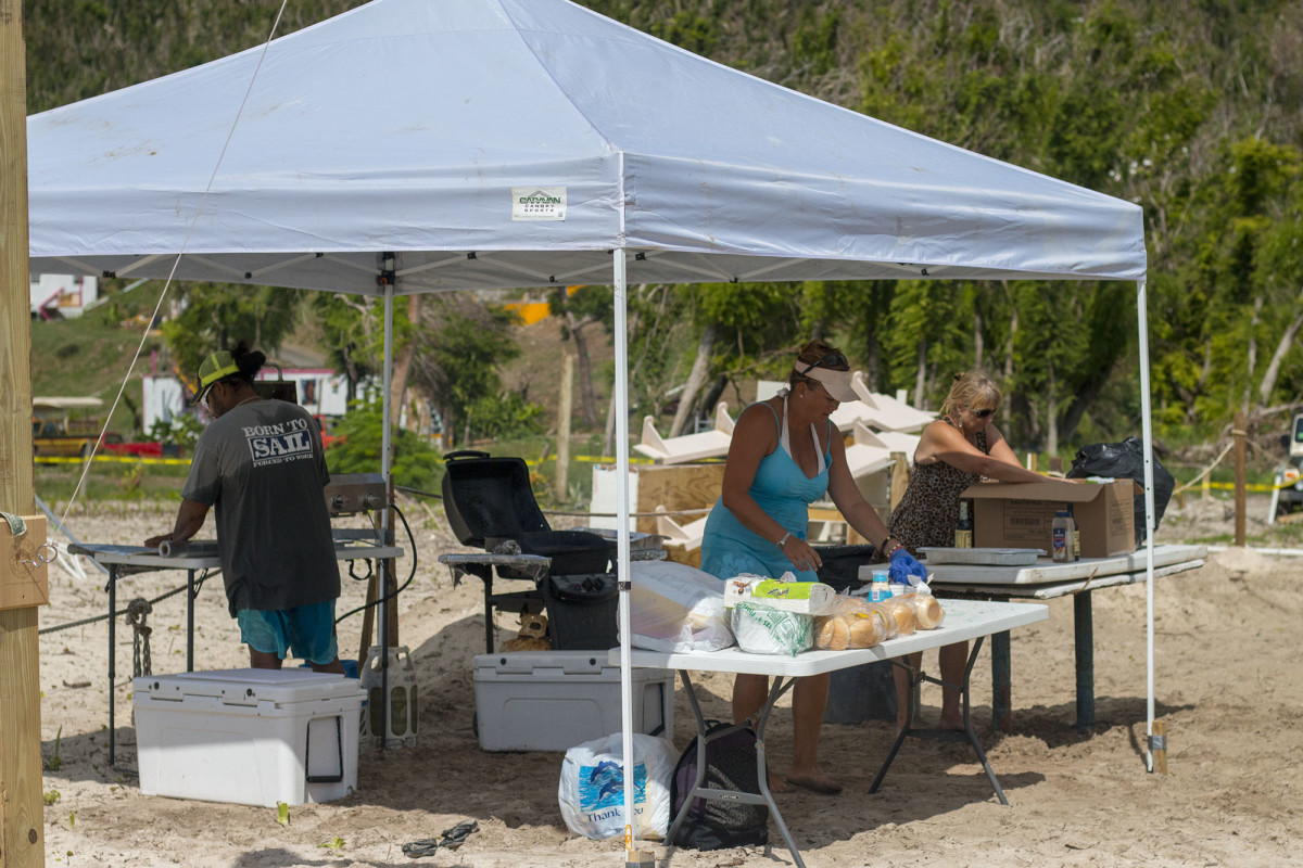 Marci Parker, her partner Chris, and a friend start preparing the BBQ which helps raise funds for the host bar.